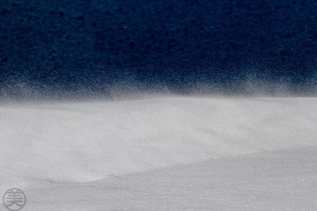 Blowing snow with dark blue surface of Crater Lake.